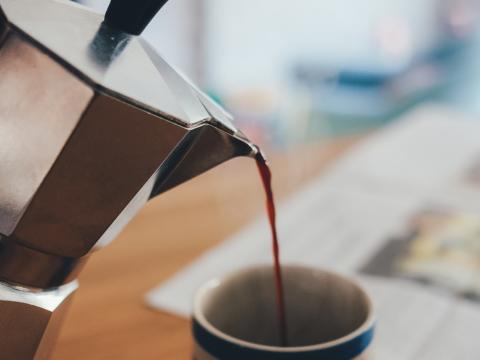 Kaffee wird aus Espressokanne in eine Kaffeetasse gegossen. JUFA Hotels bieten erholsamen Familienurlaub und einen unvergesslichen Winter- und Wanderurlaub.
