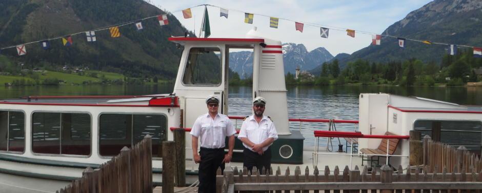 Sie sehen zwei Kapitäne vor einem Schiff am Grundlsee im Sommer. JUFA Hotels bietet tollen Sommerurlaub an schönen Seen für die ganze Familie.
