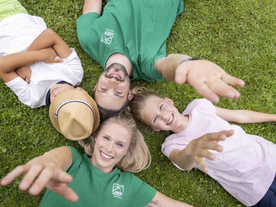 Sie sehen Kids-Club Betreuer der JUFA Hotels und zwei Kinder auf einer Wiese liegen. Sie strecken die Hände in die Höhe und lachen.