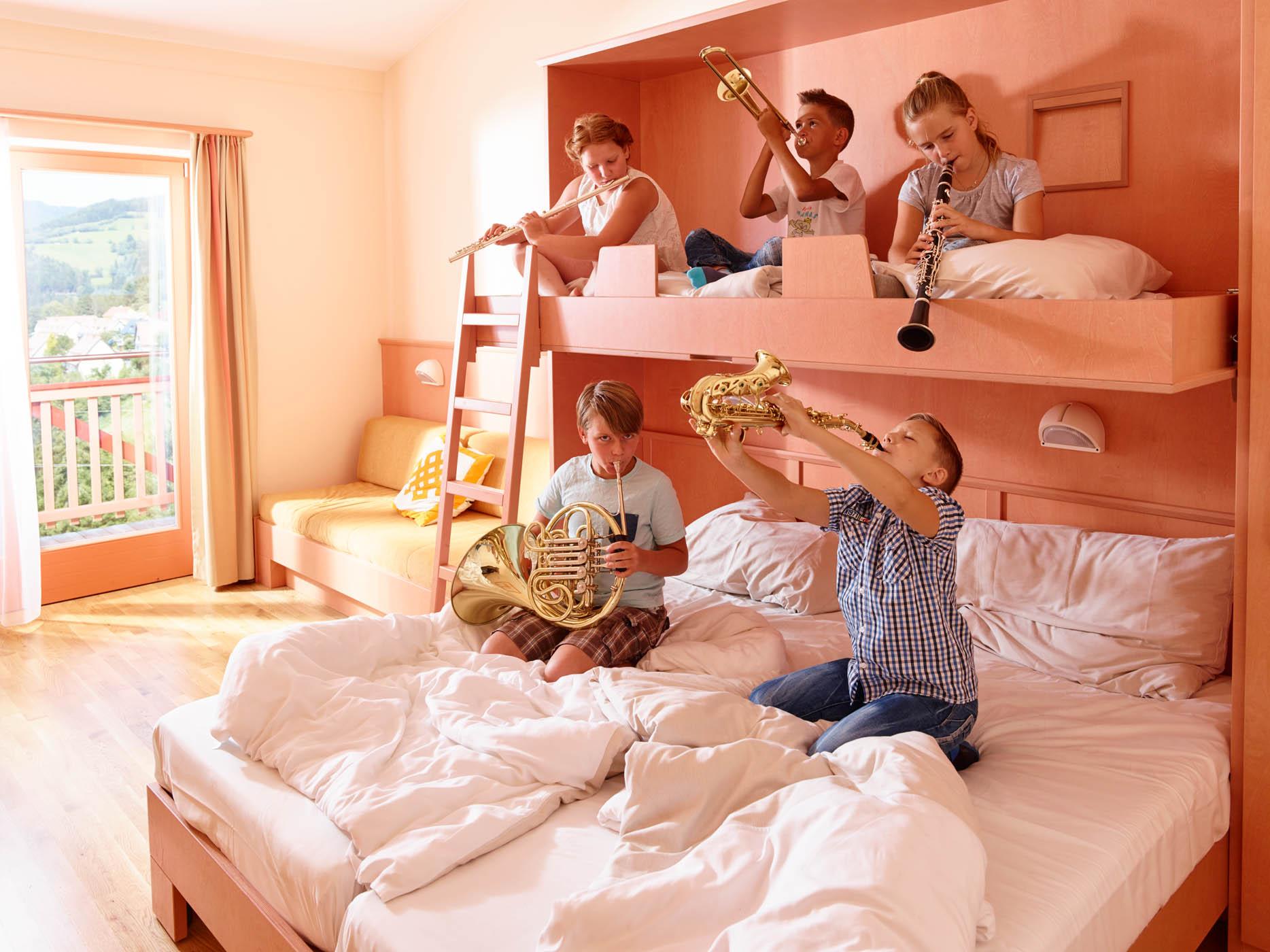 Sie sehen Kinder mit Blasmusikinstrumenten im Zimmer im JUFA Hotel Knappenberg. Der ideale Platz zum Musizieren und Singen in der Gemeinschaft in abwechslungsreichen Regionen.