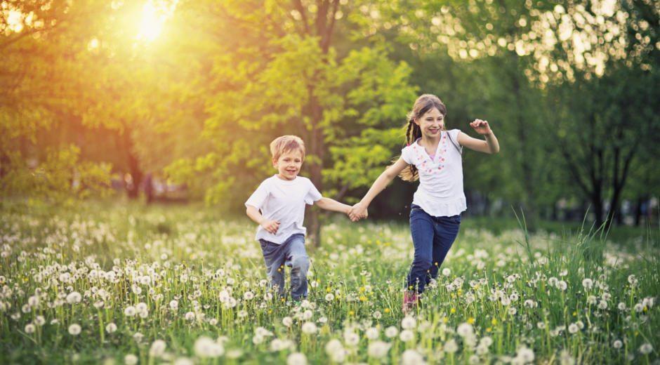 Sie sehen zwei Kinder im Sommer glücklich über eine Blumenwiese laufen. JUFA Hotels bietet kinderfreundlichen und erlebnisreichen Urlaub für die ganze Familie.