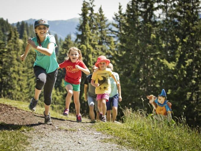 Sie sehen Kinder, die auf Montelino's Erlebnisweg in Saalbach im Sommer laufen. JUFA Hotels bietet erholsamen Familienurlaub und einen unvergesslichen Winter- und Wanderurlaub.