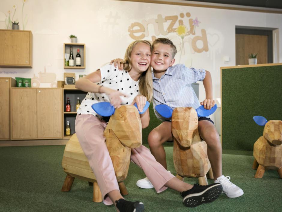 Sie sehen Kinder in der Spielecke mit Holzschafen im JUFA Hotel Weiz. Der Ort für kinderfreundlichen und erlebnisreichen Urlaub für die ganze Familie.