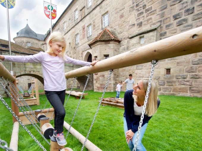 Sie sehen Kinder beim Spielen auf dem Spielplatz des JUFA Hotel Kronach – Festung Rosenberg***. Der Ort für kinderfreundlichen und erlebnisreichen Urlaub für die ganze Familie.