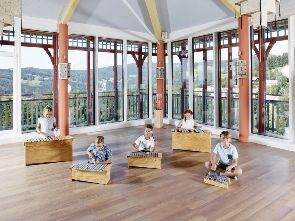 Sie sehen Kinder beim Xylophonspielen im JUFA Hotel Knappenberg. JUFA Hotels bietet den idealen Platz zum Musizieren und Singen in der Gemeinschaft in abwechslungsreichen Regionen.