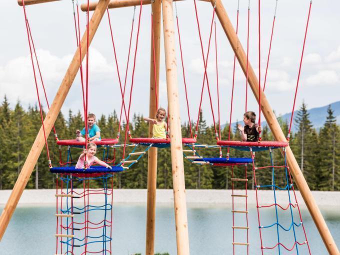 Vier Kinder sitzen auf dem Klettergerüst beim Biberwasser auf der Mariazeller Bürgeralpe. JUFA Hotels bietet kinderfreundlichen und erlebnisreichen Urlaub für die ganze Familie.