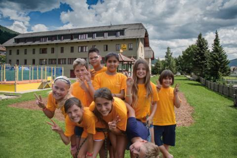 Eine Gruppe von Kindern im JUFA T-Shirt posiert auf dem Spielplatz vom JUFA Hotel Lungau für ein Foto. JUFA Hotels bieten erlebnisreiche Feriencamps mit Schwerpunkten in den Bereichen Sport, Ernährung, Bildung und Pädagogik.