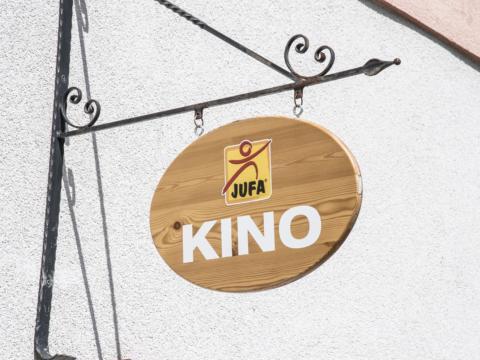 Das Kino-Schild aus Holz an der Außenfassade des JUFA Hotel Murau. Genießen Sie tolles Kinoprogramm mit Ihrer Familie im JUFA Hotel Murau.