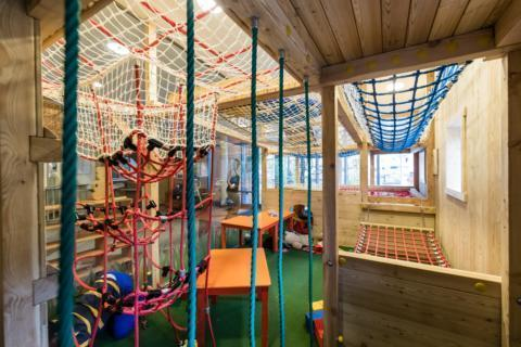 Sie sehen den Kletterbereich im JUFA Hotel Veitsch mit Kindertischen. JUFA Hotels bietet kinderfreundlichen und erlebnisreichen Urlaub für die ganze Familie.