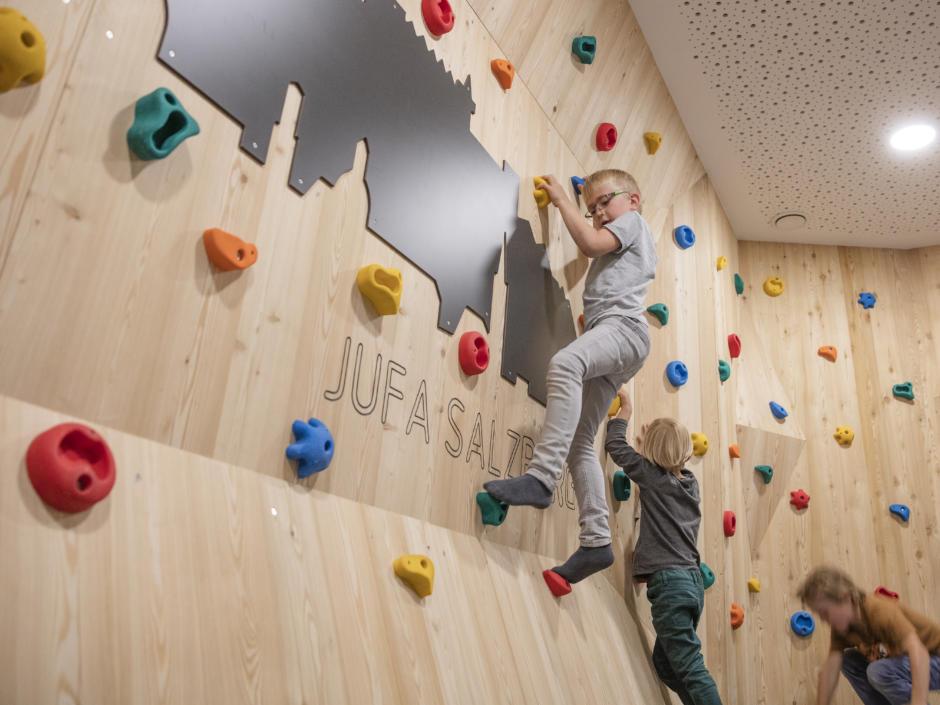 Sie sehen Kinder beim Klettern im Spielbereich im JUFA Hotel Salzburg City. Der Ort für erholsamen Familienurlaub und einen unvergesslichen Winter- und Wanderurlaub.