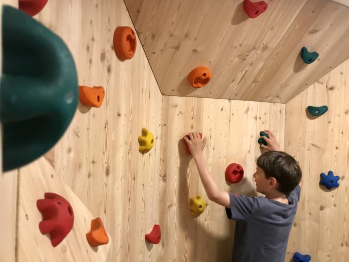 Sie sehen ein Kind an einer Kletterwand klettern im JUFA Alpenhotel Saalbach****. Der Ort für erlebnisreichen Natururlaub für die ganze Familie.