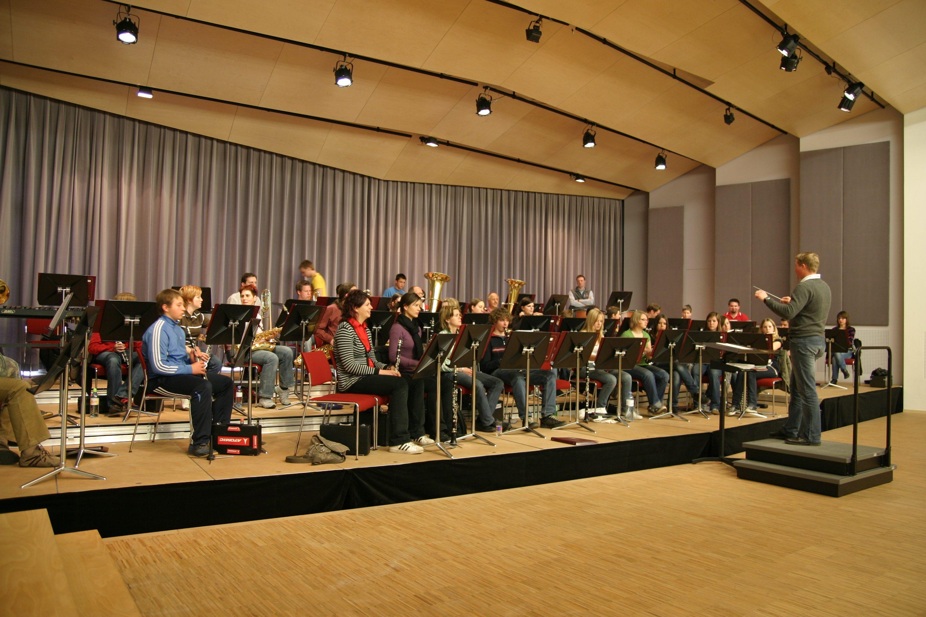 Sie sehen Konzertsaal des Musikzentrums Knappenberg mit Orchester. JUFA Hotels bietet den idealen Platz zum Musizieren und Singen in der Gemeinschaft in abwechslungsreichen Regionen.