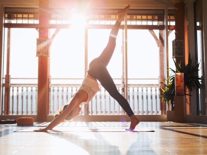 Sie sehen die Yogalehrerin Janina Brunner bei der Yoga-Figur Herabschauender Hund beim Flow Yoga Retreat im JUFA Hotel Knappenberg****. Der Ort für erholsamen Familienurlaub und einen unvergesslichen Winter- und Wanderurlaub.