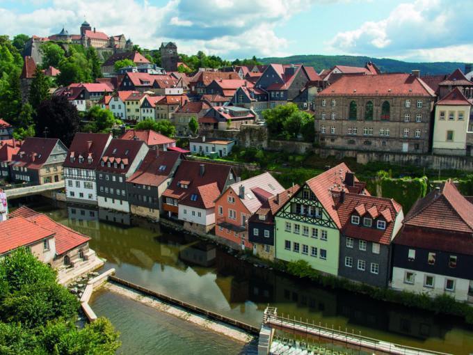 Sie sehen Kronach mit einem Fluss und der Festung Rosenberg im Sommer. JUFA Hotels bietet kinderfreundlichen und erlebnisreichen Urlaub für die ganze Familie.