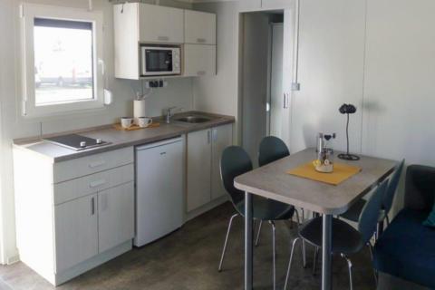 Sie sehen eine Küche in einem Mobile Home am JUFA Vulkan Thermen-Resort mit einem Tisch. JUFA Hotels bietet erholsamen Thermenspass für die ganze Familie.