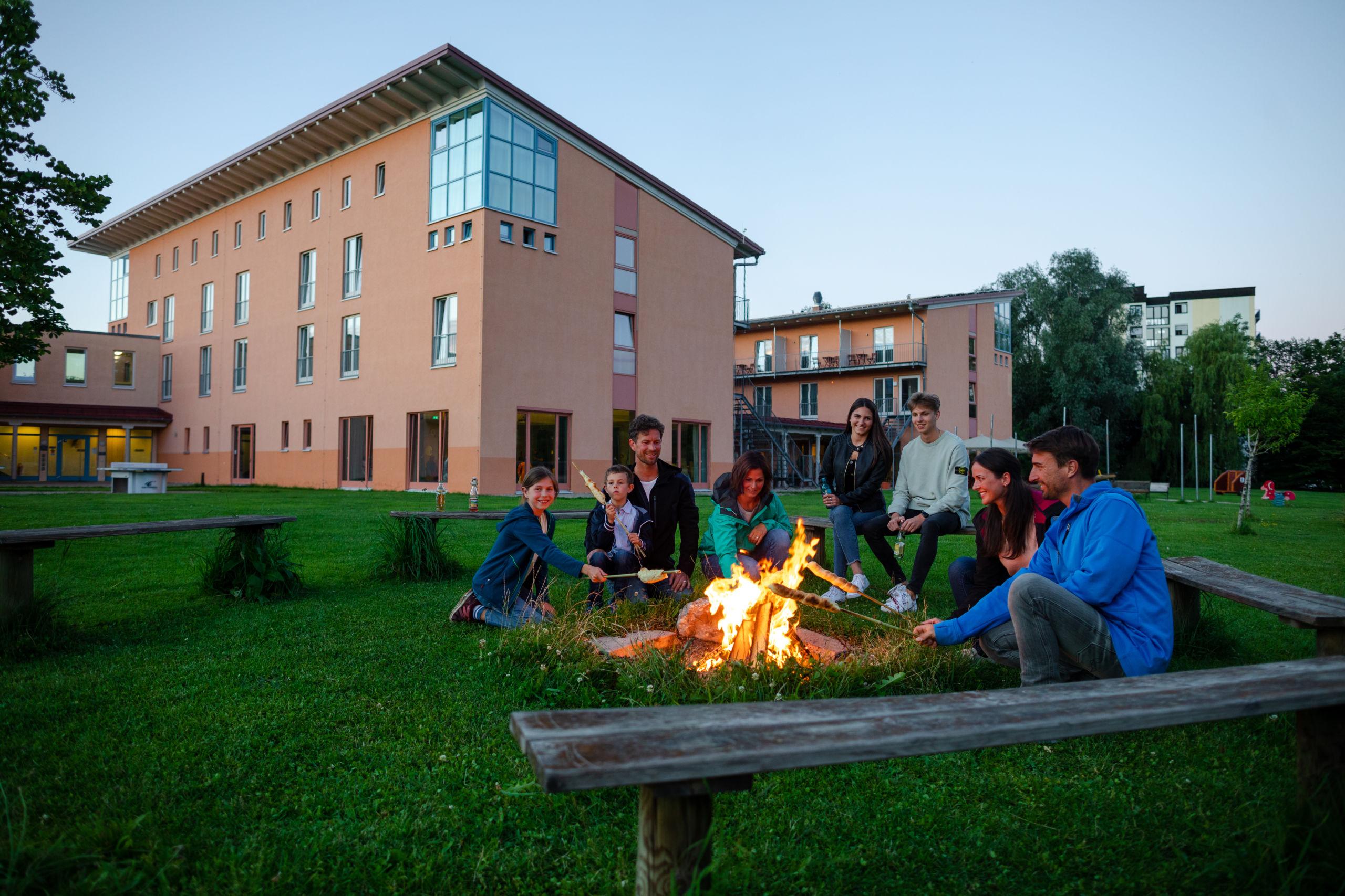 Sie sehen die Hausansicht mit Lagerfeuerstelle im Vordergrund im JUFA Kempten. Der Ort für kinderfreundlichen und erlebnisreichen Urlaub für die ganze Familie.