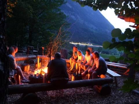 Eine Gruppe Erwachsener sitzt in Pyhrn-Priel im Wald am Lagerfeuer und grillt. JUFA Hotels bietet den Ort für erfolgreiche und kreative Seminare in abwechslungsreichen Regionen.