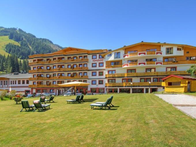 Sie sehen die Rückansicht des Alpenhotel Saalbach mit Sonnenliegen auf dem Rasen im Sommer. JUFA Hotels bietet erholsamen Familienurlaub und einen unvergesslichen Winterurlaub.