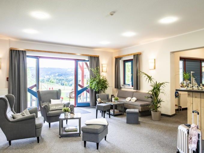 Sie sehen den gemütlichen Lobbybereich im JUFA Hotel Maria Lankowitz mit Terrasse. JUFA Hotels bietet tollen Sommerurlaub an schönen Seen für die ganze Familie.