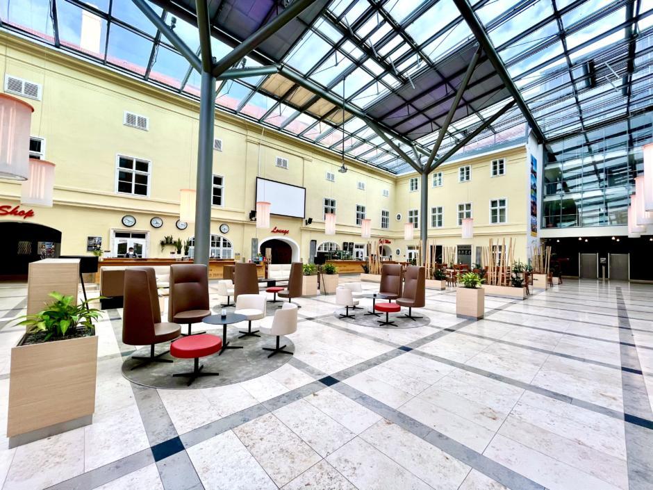 Sie sehen die Innenhof-Lobby mit Bar- und Rezeptionsbereich im JUFA Hotel Wien-City. Der Ort für erholsamen Städteurlaub in Österreich.