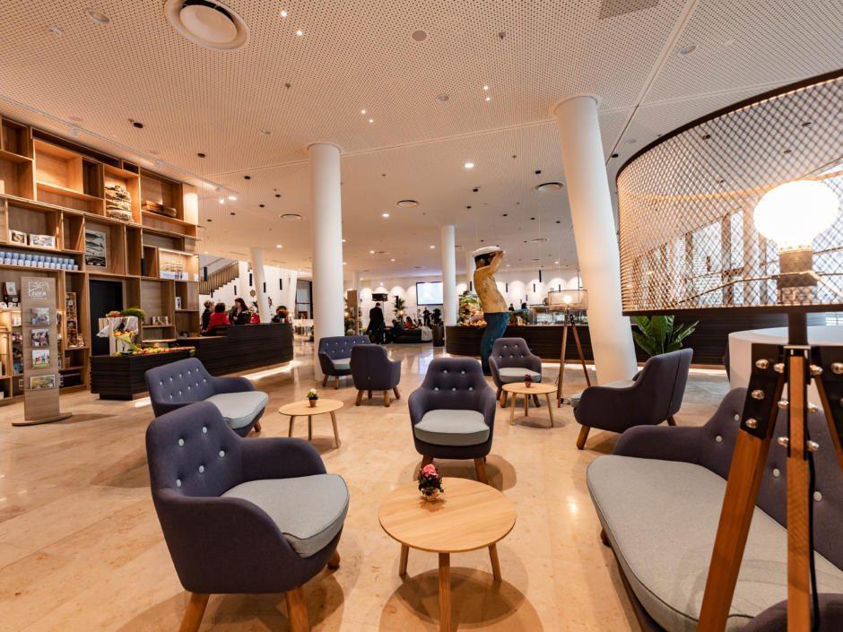 Sie sehen die Lobby mit bequemen Sesseln im JUFA Hotel Hamburg HafenCity. Der Ort für erlebnisreichen Städtetrip für die ganze Familie und der ideale Platz für Ihr Seminar.