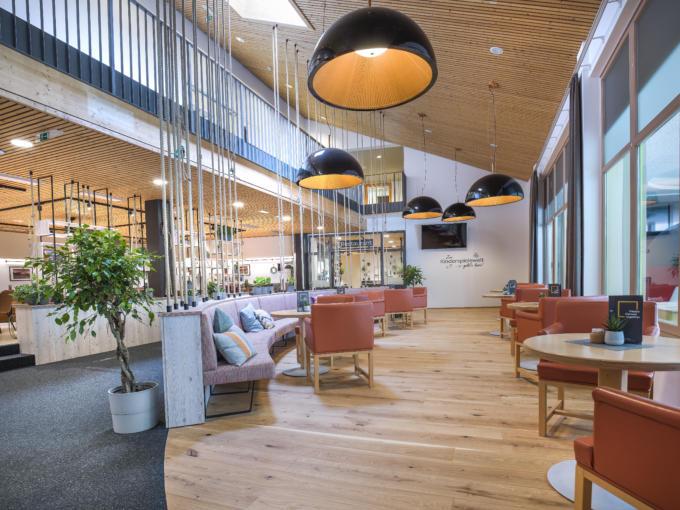 Sie sehen einen gemütlichen Lobbybereich im JUFA Hotel Wipptal. Der Ort für erholsamen Familienurlaub und einen unvergesslichen Winter- und Wanderurlaub.