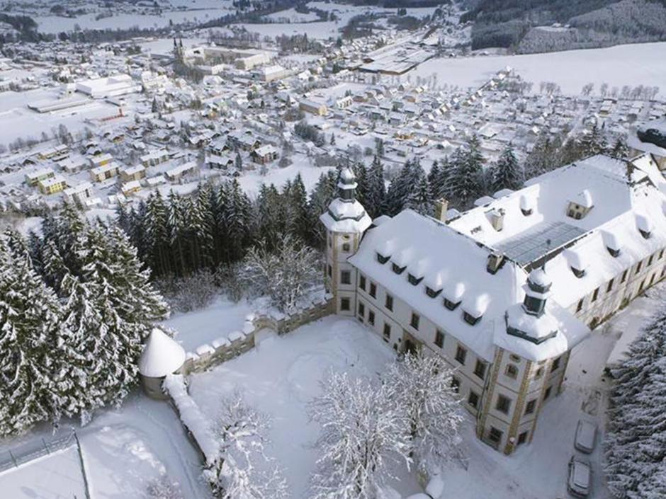 Sie sehen das JUFA Hotel Schloss Röthelstein/Admont*** mit Winterlandschaft in einer Luftaufnahme. JUFA Hotels bietet erholsamen Familienurlaub und einen unvergesslichen Winter- und Wanderurlaub.