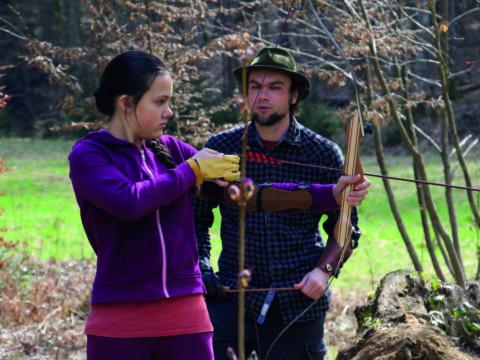 Mädchen beim Bogenschießen mit Trainer in der Natur im Herbst. JUFA Hotels bieten erholsamen Familienurlaub und einen unvergesslichen Winter- und Wanderurlaub.