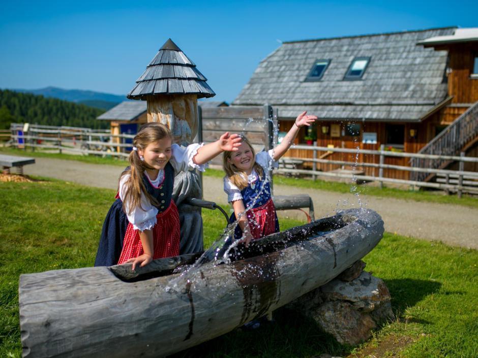 Sie sehen Mädchen im Dirndl am Brunnen beim Spielen vor der Hiaslhütte in den Nockbergen. JUFA Hotels bietet erholsamen Familienurlaub und einen unvergesslichen Winter- und Wanderurlaub.