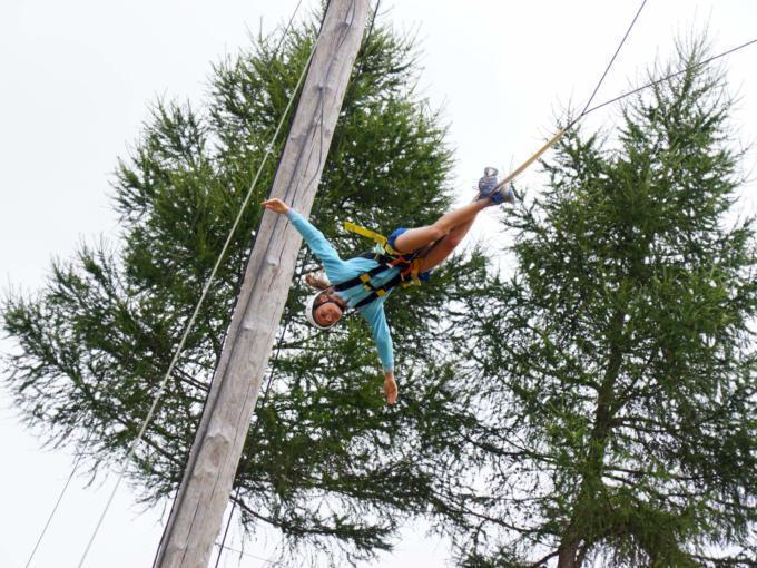 Sie sehen ein Mädchen beim Flying Fox im Outdoorparc Lungau im Sommer. JUFA Hotels bietet erlebnisreiche Feriencamps in den Bereichen Sport, Gesundheit, Bildung und Sprachen.