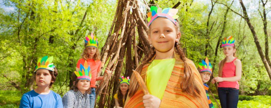 Sie sehen ein glückliches Mädchen mit Ihren Freunden im Wald, die Indianers spielen im Sommer. JUFA Hotels bietet betreute Programme für Schulen, die mit ausgebildeten BetreuerInnen und TrainerInnen durchgeführt werden.
