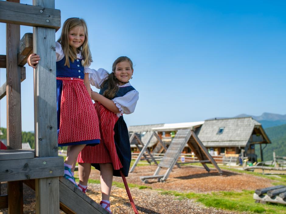 Sie sehen Mädchen im Dirndl am Spielplatz bei der Hiaslhütte in den Nockbergen. JUFA Hotels bietet erholsamen Familienurlaub und einen unvergesslichen Winter- und Wanderurlaub.