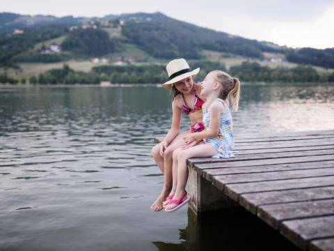 Sie sehen zwei Mädchen auf einem Steg am Stubenbergsee in Badekleidung im Sommer. JUFA Hotels bietet tollen Sommerurlaub an schönen Seen für die ganze Familie.