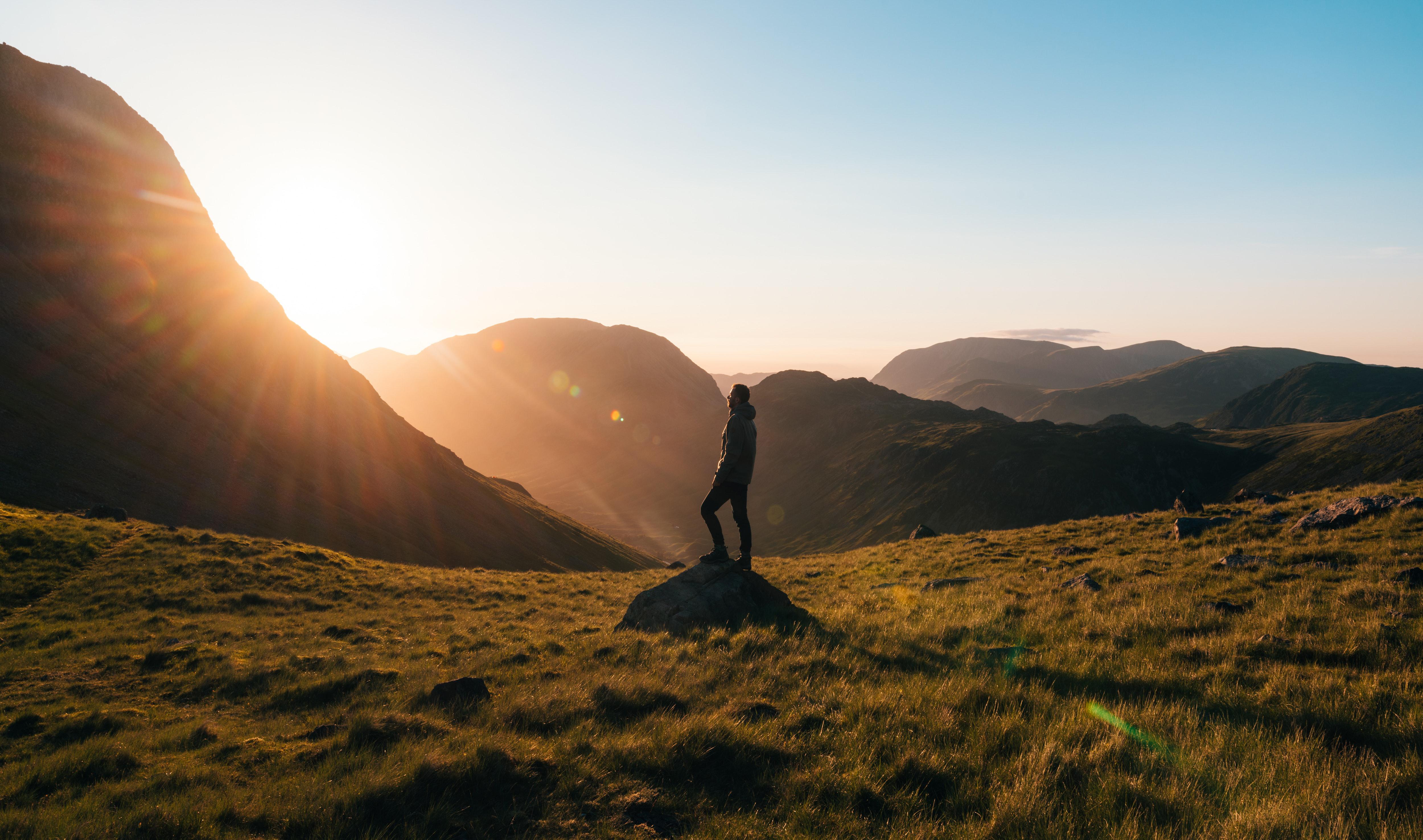 Sie sehen einen Mann auf einer Bergweise bei Sonnenaufgang. JUFA Hotels bietet Ihnen den Ort für erlebnisreichen Natururlaub für die ganze Familie.