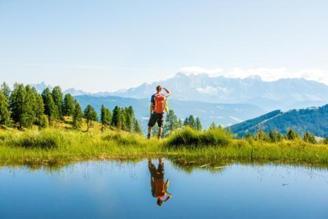 Sie sehen einen Mann beim Wandern im Salzburger Land mit herrlichem Bergpanorama. JUFA Hotels bietet erholsamen Familienurlaub und einen unvergesslichen Winter- und Wanderurlaub.