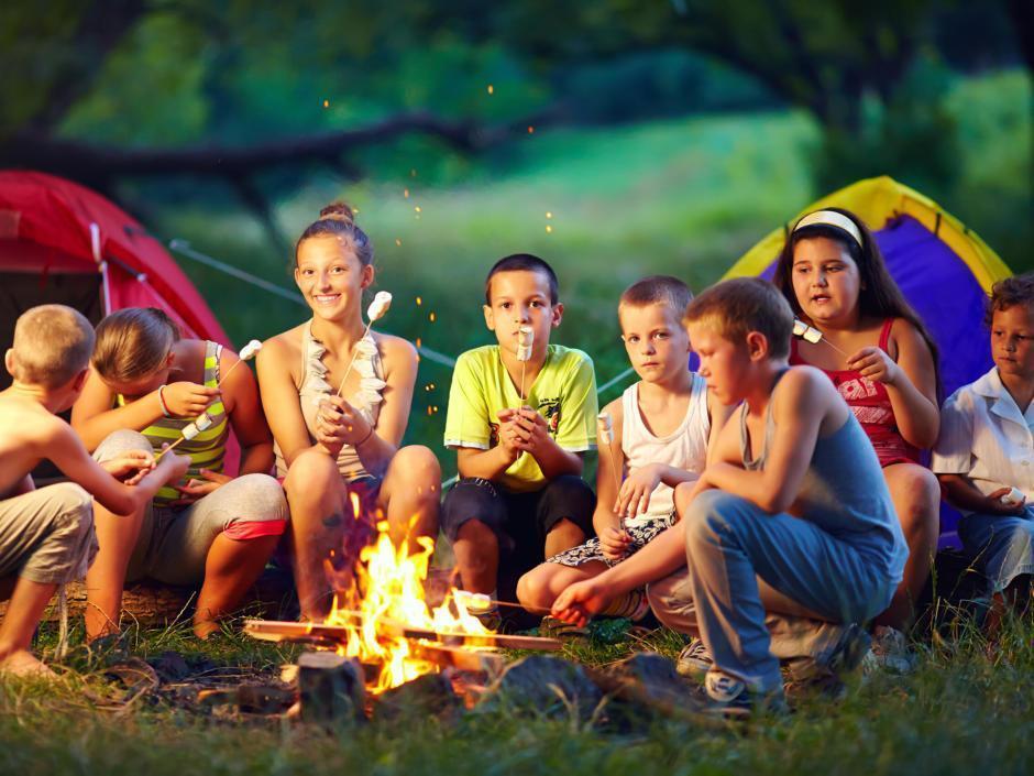 Kinder beim grillen Marshmallows über einem Lagerfeuer in der Natur bei Abendstimmung. JUFA Hotels bietet erlebnisreiche Feriencamps in den Bereichen Sport, Gesundheit, Bildung und Sprachen.