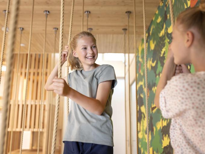 Sie sehen zwei Mädchen im Indoor-Spielbereich des JUFA Hotel Savognin***s.