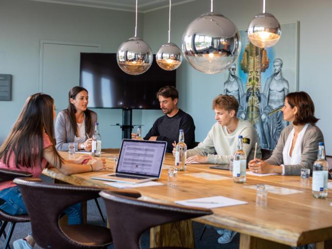 Sie sehen eine Gruppe von Menschen im Seminarraum Tiberius im Gespräch. JUFA Hotels bietet den Ort für erfolgreiche und kreative Seminare in abwechslungsreichen Regionen.