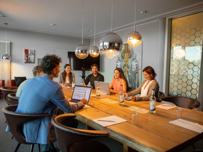 Sie sehen eine Gruppe von Menschen im Seminarraum Tiberius. JUFA Hotels bietet den Ort für erfolgreiche und kreative Seminare in abwechslungsreichen Regionen.