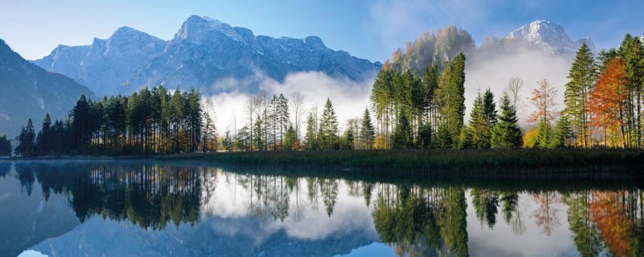 Sie sehen eine Landschaftsaufnahme von Mission Grüner Planet mit See, Bäumen und Gebirge im Hintergrund. JUFA Hotels bietet Ihnen den Ort für erlebnisreichen Natururlaub für die ganze Familie.