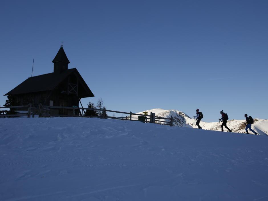 Sie sehen Schneeschuhwanderer an einer Bergkapelle im Murtal im Winter. JUFA Hotels bietet erholsamen Familienurlaub und einen unvergesslichen Winterurlaub.