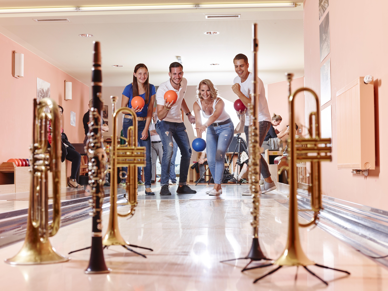 Sie sehen Musiker beim Bowling im JUFA Hotel Knappenberg mit Instrumenten. JUFA Hotels bietet den idealen Platz zum Musizieren und Singen in der Gemeinschaft in abwechslungsreichen Regionen.