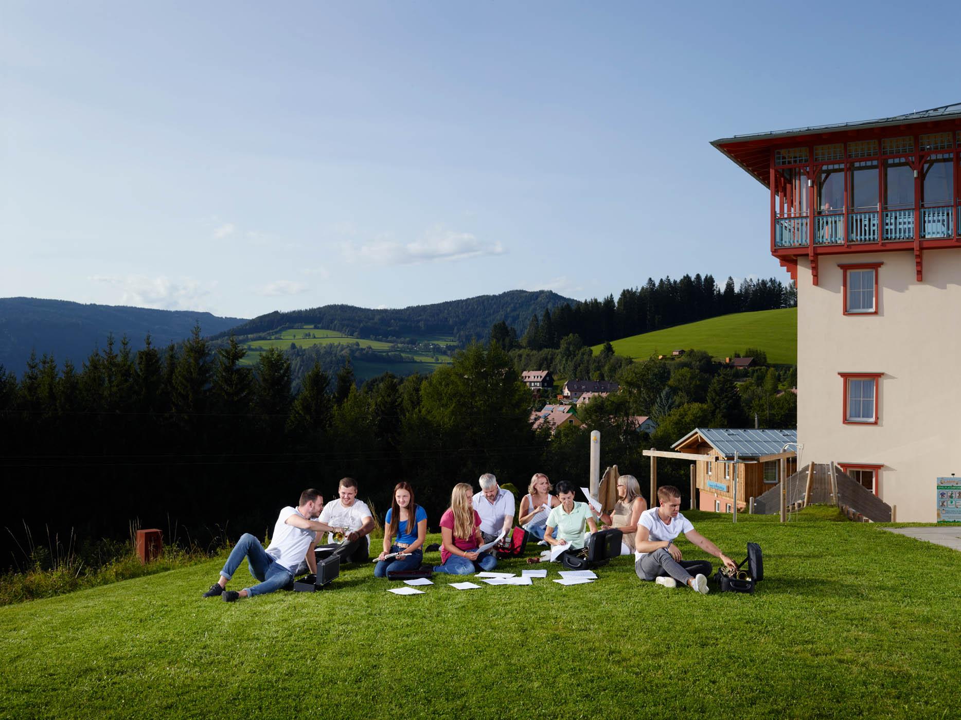 Sie sehen eine Gruppe Musiker im JUFA Hotel Knappenberg auf einer Wiese im Sommer. JUFA Hotels bietet den idealen Platz zum Musizieren und Singen in der Gemeinschaft in abwechslungsreichen Regionen.