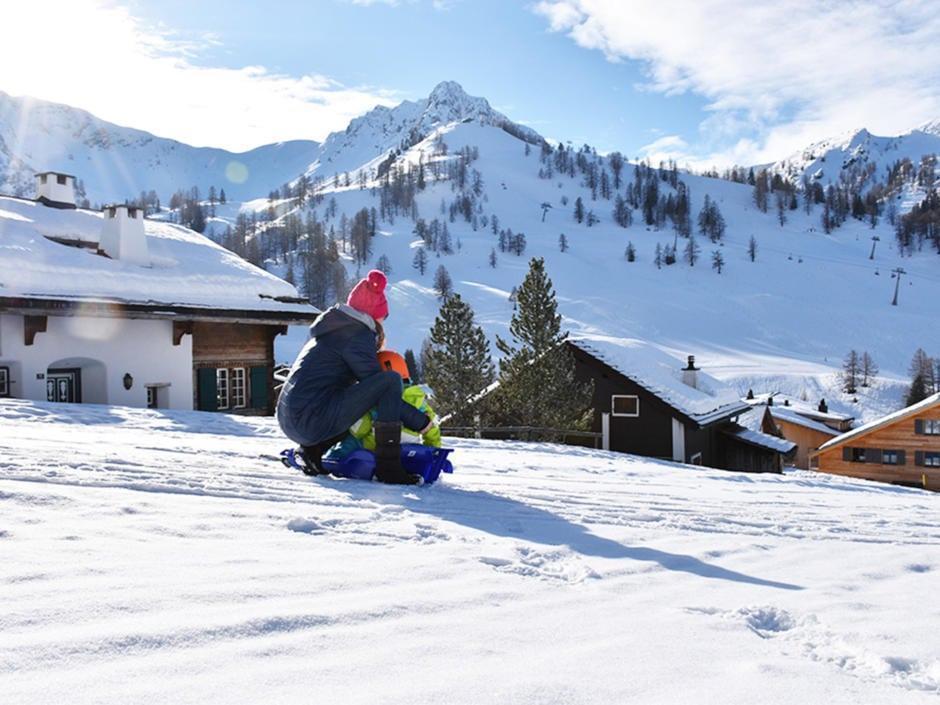 Sie sehen eine Mutter mit ihrem Kind beim Rodeln am JUFA Hotel Malbun – Alpin-Resort***. Der Ort für erholsamen Familienurlaub und einen unvergesslichen Winterurlaub.