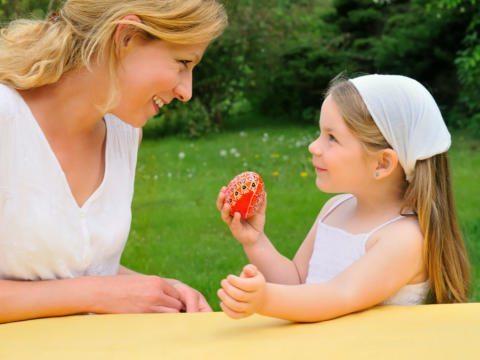 Mutter mit Mädchen und Osterei im Garten. JUFA Hotels bietet Ihnen den Ort für erlebnisreichen Natururlaub für die ganze Familie.