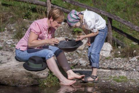 Sie sehen eine Mutter und ihre Tochter beim Goldwaschen in Pusterwald in der Steiermark. JUFA Hotels bietet kinderfreundlichen und erlebnisreichen Urlaub für die ganze Familie.