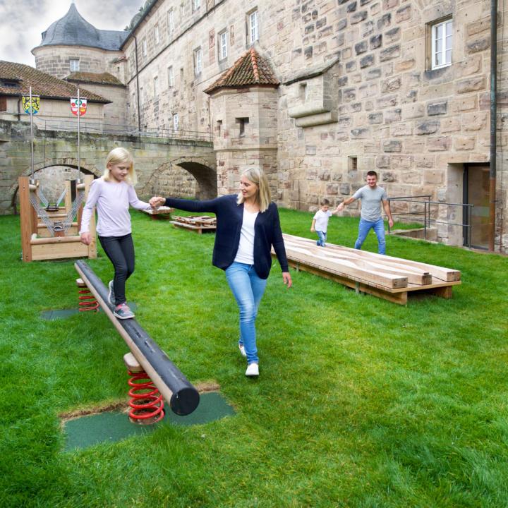 Sie sehen eine Mutter und Tochter auf dem Spielplatz vor dem JUFA Hotel Kronach – Festung Rosenberg***. Der Ort für kinderfreundlichen und erlebnisreichen Urlaub für die ganze Familie.
