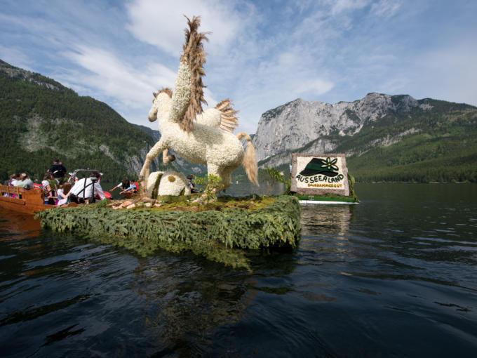 Sie sehen eine Pferdeblumenfigur auf dem Grundlsee während des Bootskorso. JUFA Hotels bietet kinderfreundlichen und erlebnisreichen Urlaub für die ganze Familie.