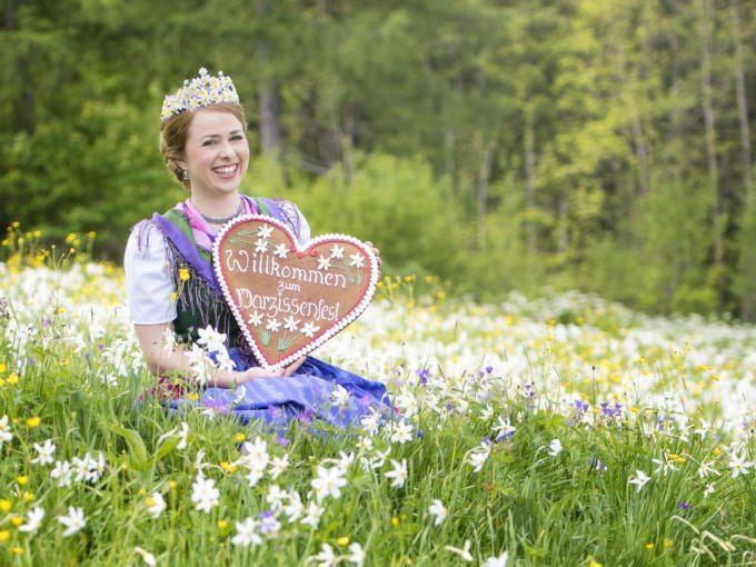 Sie sehen die Narzissenkönigin mit einem Lebkuchenherz in einer Blumenwiese. JUFA Hotels bietet kinderfreundlichen und erlebnisreichen Urlaub für die ganze Familie.