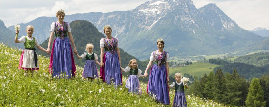 Sie sehen die Narzissenkönigin mit den Prinzessinnen und Kindern in einer Blumenwiese. JUFA Hotels bietet kinderfreundlichen und erlebnisreichen Urlaub für die ganze Familie.